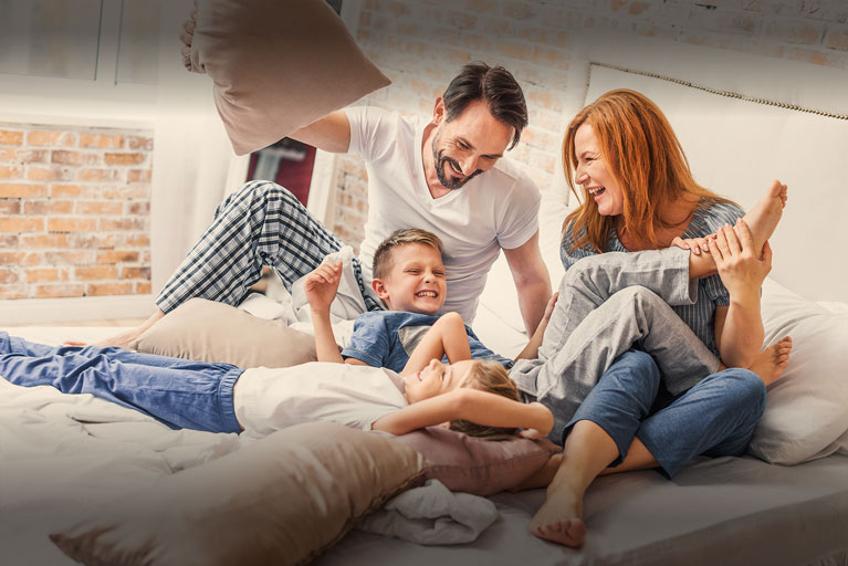 Banner Image | Young family having a pillow fight.